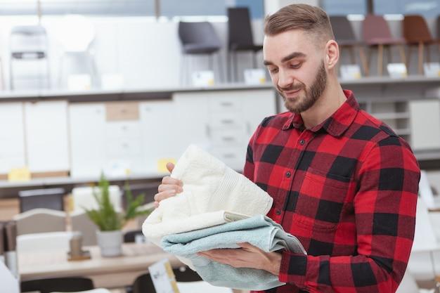 Uroczy brodaty młody człowiek robi zakupy bielizny domowej w sklepie z meblami
