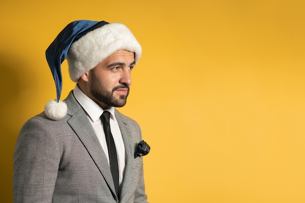 Uroczy brodaty młody człowiek w niebieskim kapeluszu i szarym garniturze mikołaja, patrząc z ukosa na białym tle na żółtej ścianie