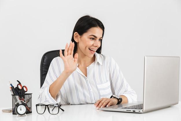 Uroczy brunetka bizneswoman siedzi przy stole z papeterii i za pomocą laptopa w biurze na białym tle nad białą ścianą
