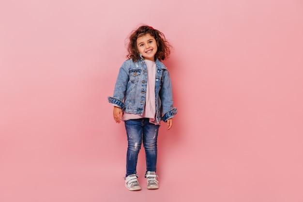 Uroczy brunetka dzieciak w dżinsowym stroju uśmiecha się do kamery. pełny widok długości szczęśliwy preteen dziewczyna na białym tle na różowym tle.