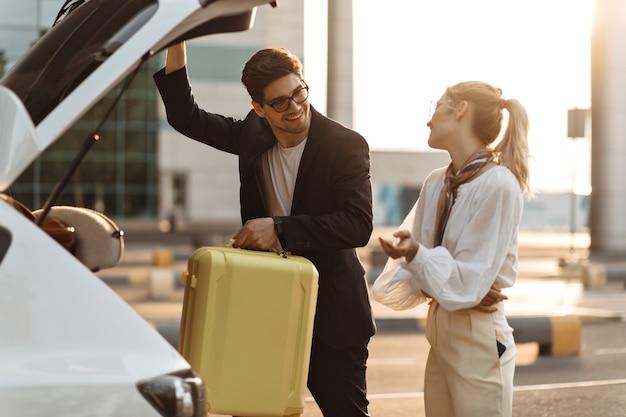 Uroczy brunetka mężczyzna w okularach przeciwsłonecznych, czarny garnitur patrzy na dziewczynę z uśmiechem i wkłada żółtą walizkę do bagażnika samochodu