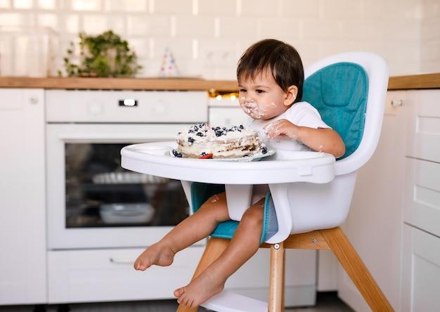 Uroczy chłopczyk obchodzi pierwsze urodziny i je pierwszy tort. urodziny dla dzieci ozdobione balonami. dziecko je ciasto.