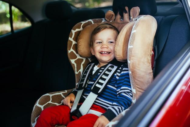 Uroczy chłopczyk w foteliku samochodowym