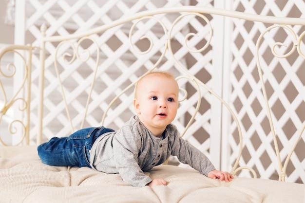 Uroczy chłopczyk w słonecznej sypialni