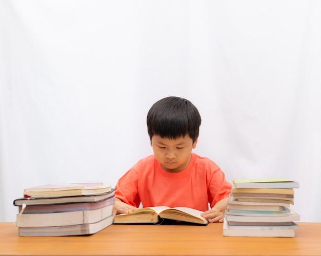 Uroczy chłopiec czyta książkę na stole i białym tle,