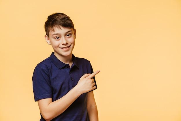 Uroczy chłopiec o brązowych oczach ubrany w ciemnoniebieską koszulkę, z szerokim uśmiechem wskazuje palcem wskazującym przestrzeń kopiowania, jest w dobrym nastroju i aprobuje wybór. koncepcja sprzedaży