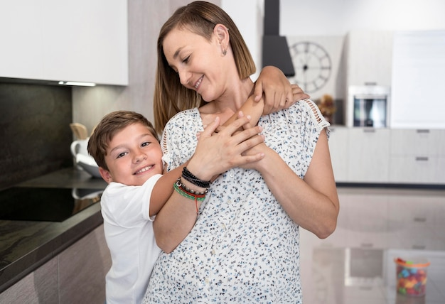 Uroczy chłopiec przytula swoją matkę w domu
