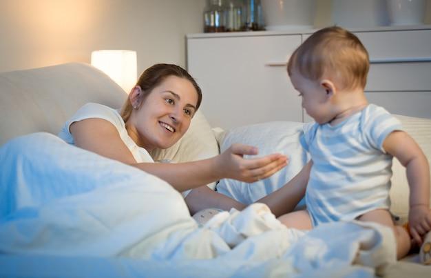 Uroczy chłopiec siedzi na łóżku w nocy i patrzy na matkę