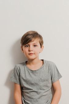 Uroczy chłopiec stojący obok białej ściany, szara koszula, z uśmiechem