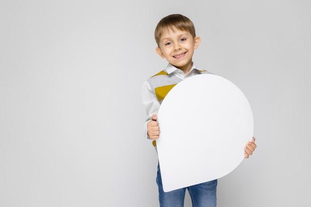 Uroczy chłopiec w białej koszuli, pasiastym bezrękawniku i jasnych dżinsach stoi na szaro
