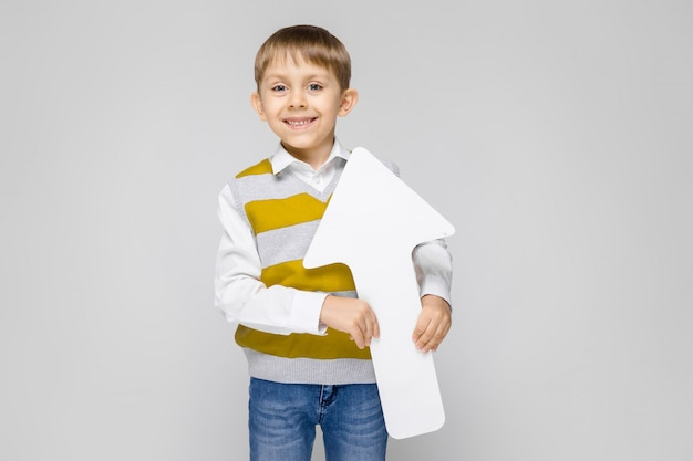 Uroczy chłopiec w białej koszuli, pasiastym podkoszulku i jasnych dżinsach stoi na szarym tle.