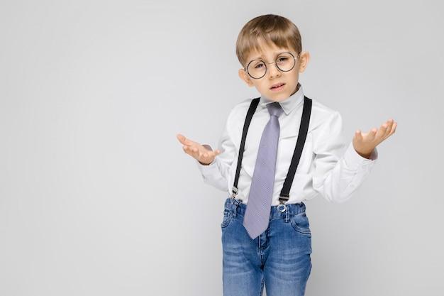 Uroczy chłopiec w białej koszuli, szelkach, krawacie i jasnych dżinsach stoi na szarym tle. chłopiec rozłożył ręce w obu kierunkach