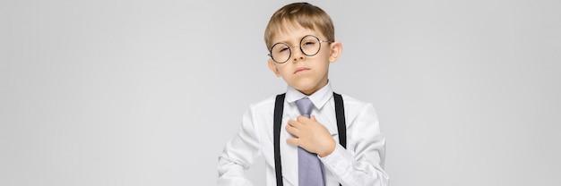 Uroczy chłopiec w białej koszuli, szelkach, krawacie i jasnych dżinsach stoi na szarym tle. chłopiec uśmiecha się i trzyma krawat za rękę