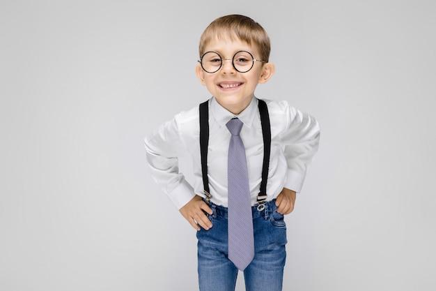 Uroczy chłopiec w białej koszuli, szelkach, krawacie i jasnych dżinsach stoi na szarym tle. chłopiec w okularach uśmiecha się