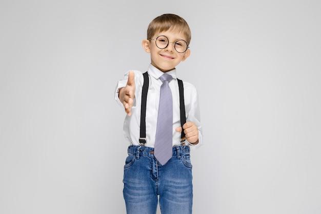 Uroczy chłopiec w białej koszuli, szelkach, krawacie i jasnych dżinsach stoi na szarym tle. chłopiec wyciąga rękę do przodu
