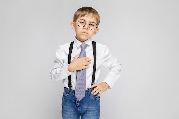 Uroczy chłopiec w białej koszuli, szelkach, krawacie i jasnych jeansach. chłopiec uśmiecha się i trzyma krawat za rękę