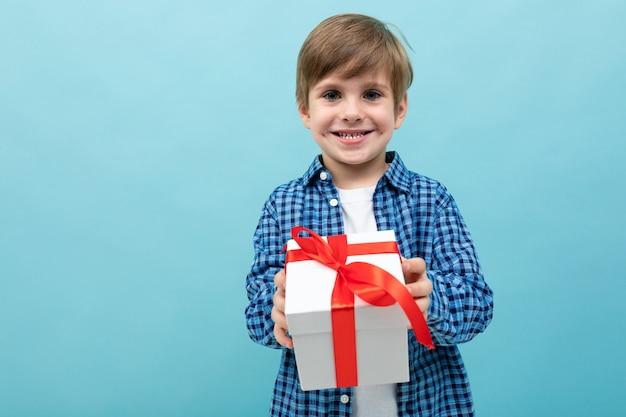 Uroczy chłopiec w kraciastej koszuli wyciąga prezent swojego kochanka na jasnoniebieskim tle