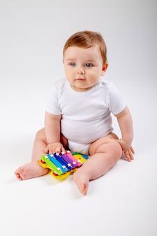 Uroczy chłopiec w wieku 8 miesięcy w białym body bawi się rozwijającym się zabawkowym siedzeniem