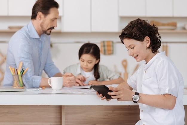 Uroczy chłopiec z falującymi włosami siedzący przy kuchennym blacie i oglądający zabawny film na swoim tablecie, podczas gdy jego ojciec i siostra robią rachunki