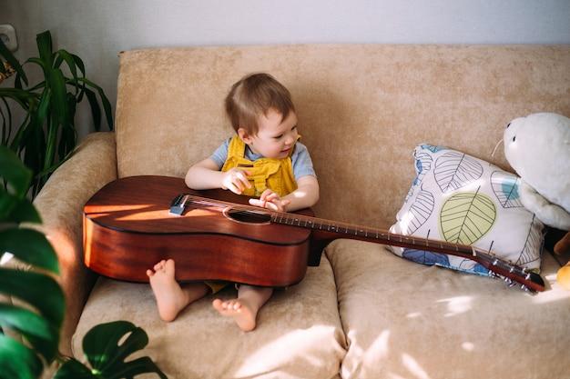 Uroczy dzieciak bawi się w domu na kanapie wielką gitarą akustyczną.