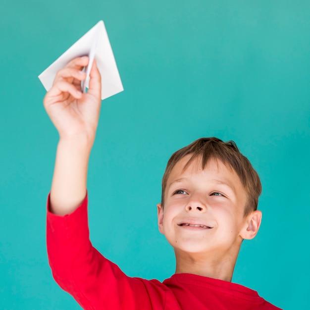 Uroczy dzieciak bawić się z papierowym samolotem