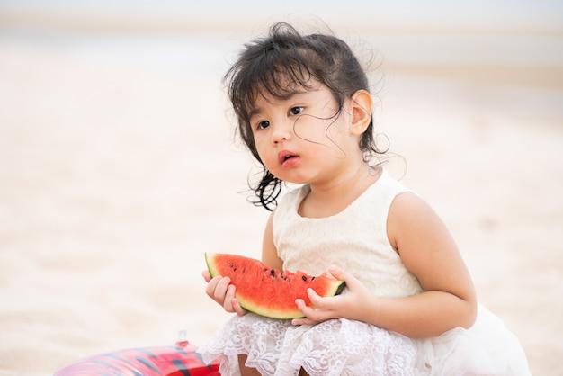 Uroczy dzieciak je arbuza na plaży.