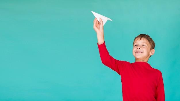 Uroczy dzieciak trzyma papierowego samolot z kopii przestrzenią
