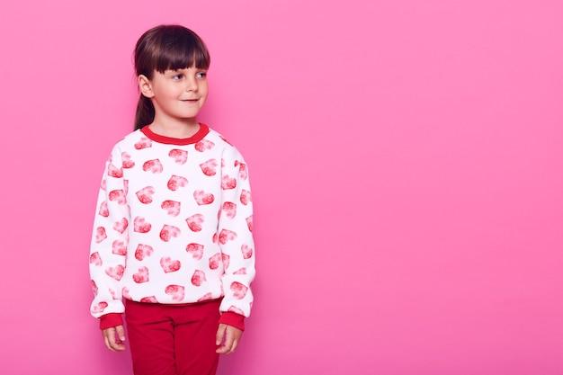 Uroczy dzieciak w swobodnym swetrze i spodniach odwracający wzrok z uroczym uśmiechem na białym tle nad różową ścianą