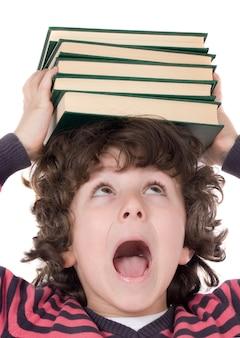 Uroczy dziecko z wiele książkami na głowie odizolowywającej nad bielem