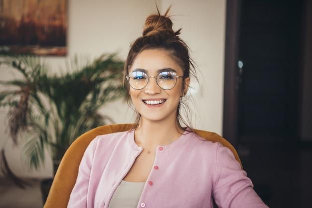 Uroczy kaukaski bizneswoman z okularami, siedząc na krześle w domu
