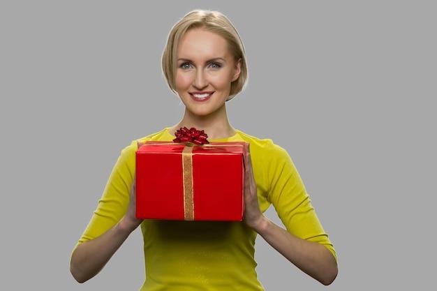 Uroczy kaukaski dama trzyma pudełko. portret pięknej uśmiechnięta kobieta z obecnym pudełkiem na szarym tle, widok z przodu. koncepcja biznesowa premii rabatów.