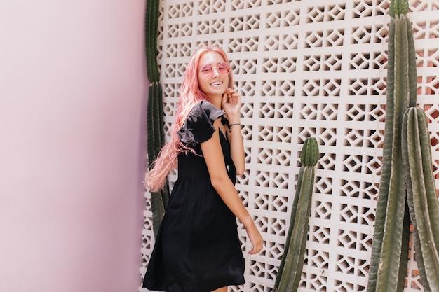 Uroczy kaukaski jasnowłosa kobieta pozuje w czarnej sukni w pobliżu kaktusa.