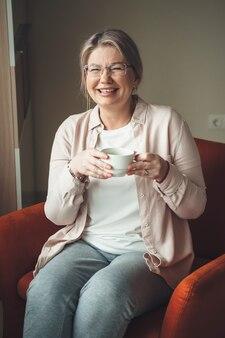 Uroczy kaukaski kobieta starszy w okularach, pije herbatę i siedzi na kanapie