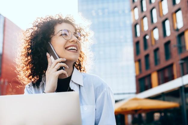 Uroczy kaukaski kobieta z kręconymi włosami rozmawia przez telefon podczas pracy na swoim komputerze
