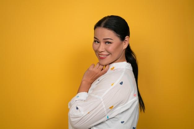 Uroczy kobieta azji uśmiechając się do kamery. śliczne wycięcie modelki w średnim wieku na żółtym tle. skopiuj miejsce.