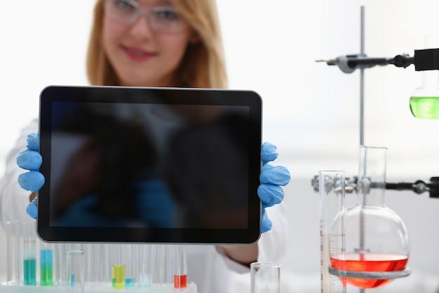 Uroczy kobieta lekarz trzymając tablet z czarnym wyświetlaczem