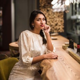 Uroczy kobieta siedzi w barze licznik