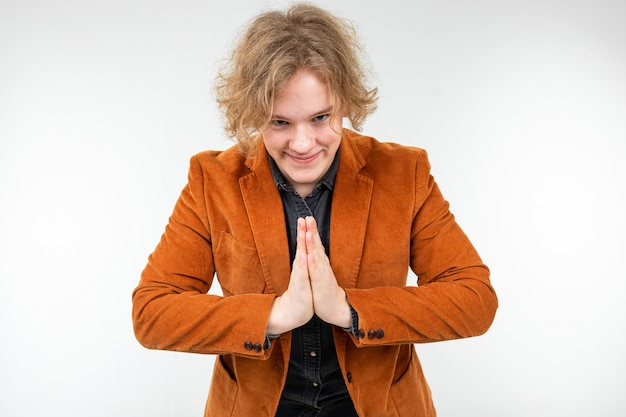Uroczy, kręcony blondyn w brązowej kurtce modli się i prosi o białe studio
