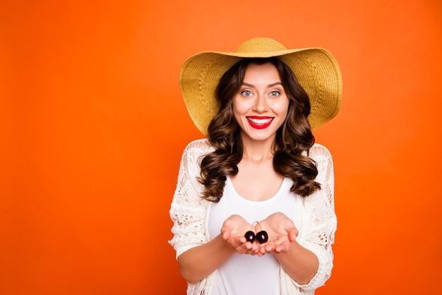 Uroczy ładny brązowowłosy ładny słodki miły kobieta uśmiechnięta ząbkowato szminka trzymając wiśnie rękami.
