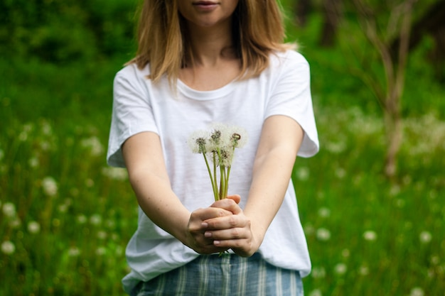 Uroczy letni obrazek kobiety trzyma dandelion przeciw trawy przestrzeni