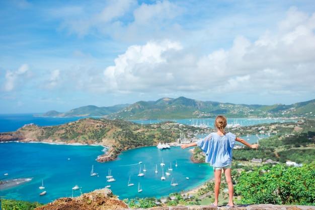 Uroczy małe dziecko cieszy się widok malowniczego angielskiego schronienie przy antigua na morzu karaibskim