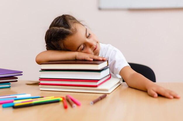Uroczy małej dziewczynki dosypianie na stercie książki nad białym tłem