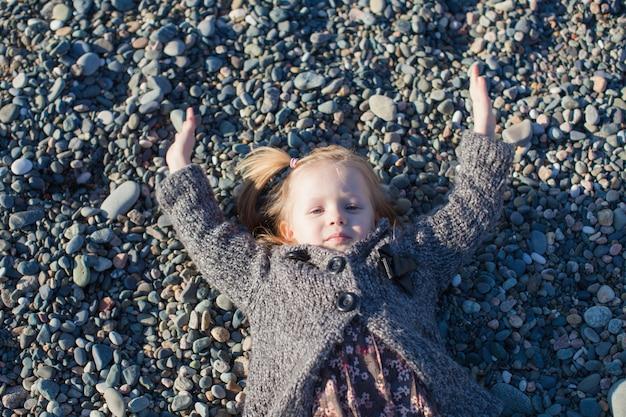 Uroczy małej dziewczynki lying on the beach na plaży w zima słonecznym dniu