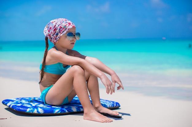 Uroczy małej dziewczynki obsiadanie na surfboard przy seashore