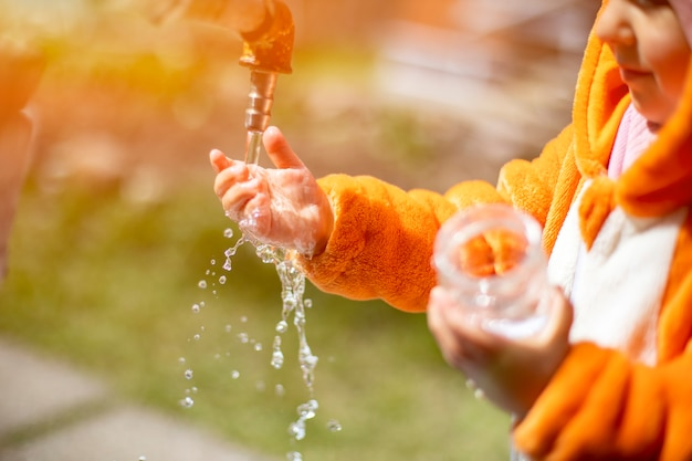 Uroczy maluch bawi się wodą i kranem w słońcu