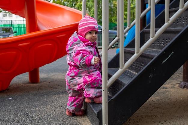 Uroczy maluch wspina się po schodach na plac zabaw. maluch dziecko ubrane w kombinezon. jesień lub zima, zimna pora roku