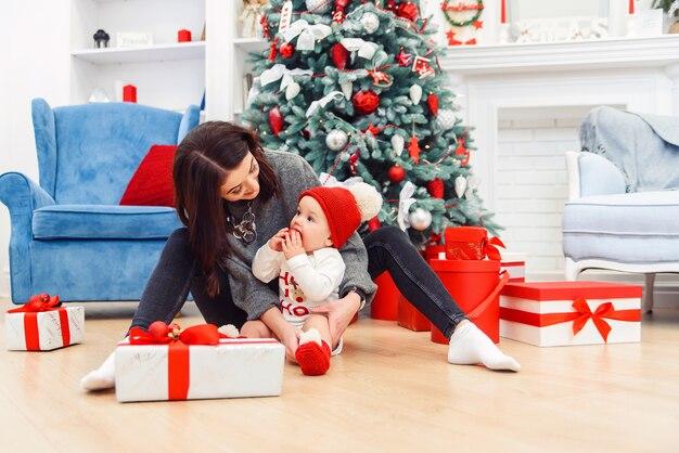 Uroczy maluch z matką rozpakowujący świąteczny prezent.