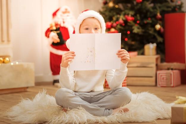 Uroczy mały artysta w czapce świętego mikołaja siedzący na podłodze i chowający się za swoim nowym arcydziełem z choinką na nim.