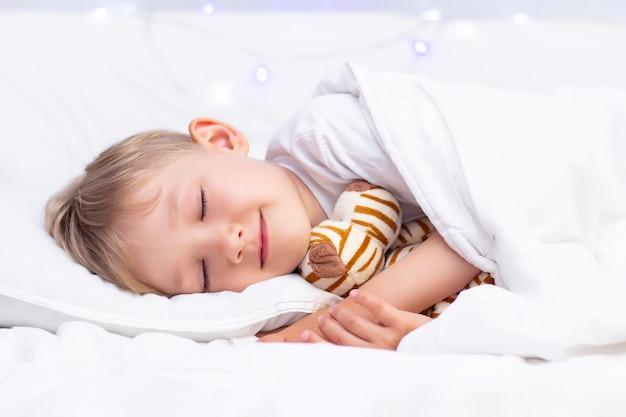 Uroczy mały biały chłopiec śpi w łóżku. przytula miękką zabawkę