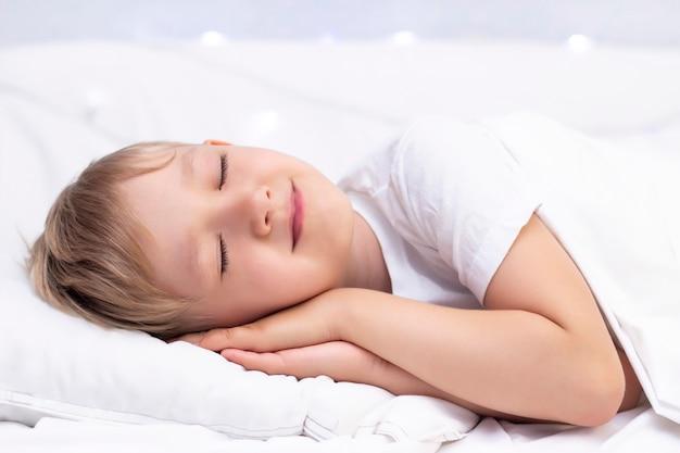 Uroczy mały biały chłopiec śpi w łóżku.